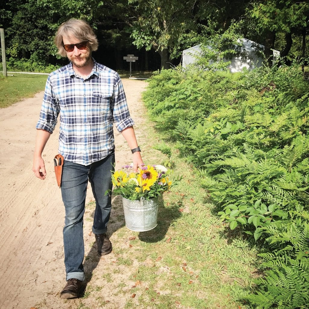 There is a local flower movement that is gaining momentum here in northern Michigan. Marc Green (pictured here) working on the flower farm he shares with partner, Jamie Platte, owner of Pontius Flower Shop. Flower growers in the area take great pride in producing flowers grown without chemicals. (Courtesy photo)