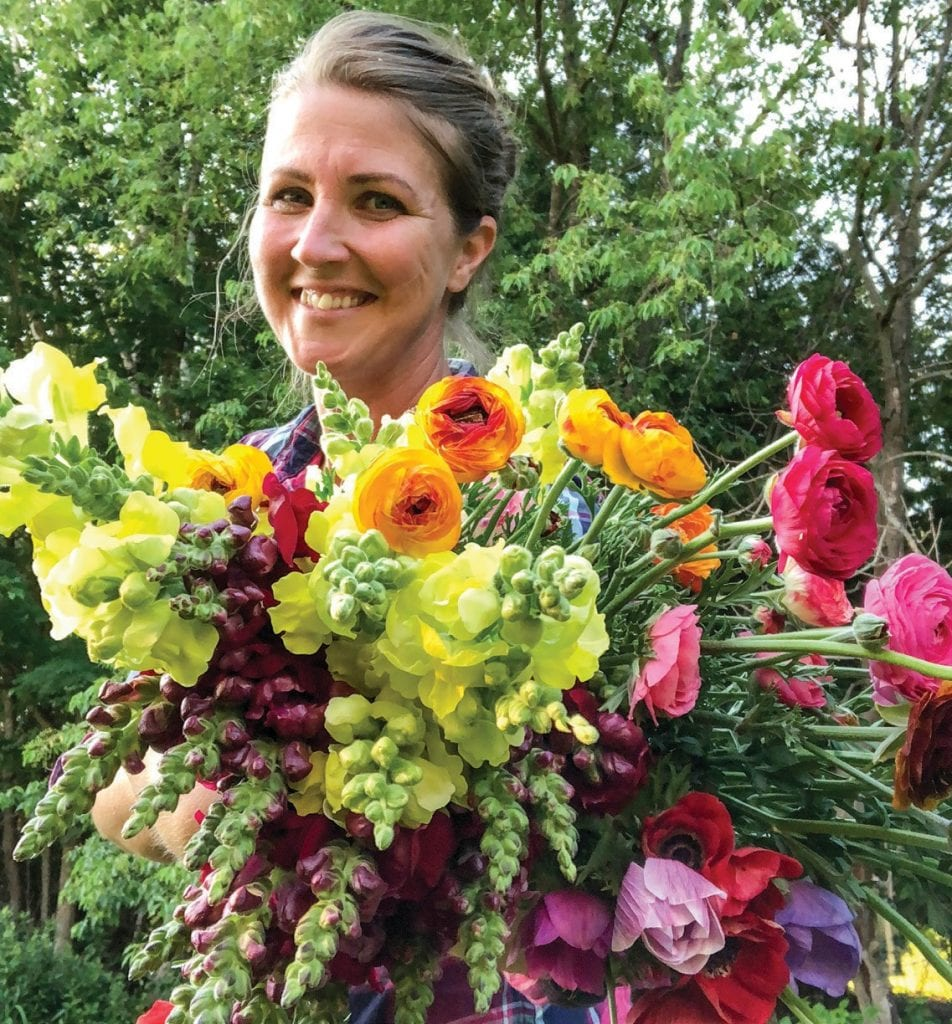 Katie MacGregor, owner of Tag-Along Flower Farm, pictured here with a few of her harvested blooms. MacGregor loves being surrounded by flowers and generations of family on her farm. (Photo courtesy of Katie MacGregor)